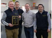 Richard Gill, Chris Swan, Barry Browne and Drea Questari holding their award.